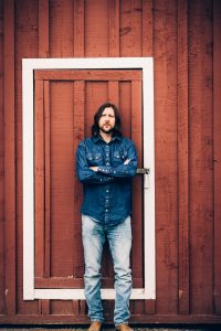 Full body picture of Graham in all denim in front of a brown wooden background with a white framed door.
