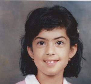 Catarina Rivera as a young girl with her hearing aids and a toothy grin.
