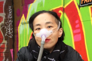 Alice Wong, and Asian American woman in a wheelchair. She is wearing a black jacket with a black patterned scarf. She is wearing a mask over her nose with a tube for her Bi-Pap machine. Behind her is a wall full of colorful street art