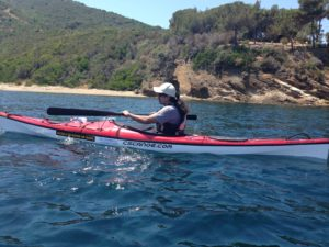 Ahmet in his kayak on a blue sea with a beautiful beach in the background.