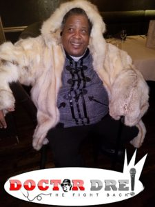 Picture of Doctor Dre, seated with a tan fur jacket with the caption, Doctor Dre The Fight Back!