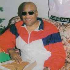 A picture of Joe Capers, an African American man seated on a couch staring into the camera with sunglasses!