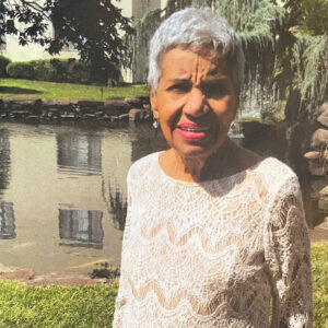 Marcelina Reid, my mom, a tan skin woman with salt and pepper short hair standing in an off white and tan lace dress, poses in front of a stream with low green shrubs with a building reflected in the water.
