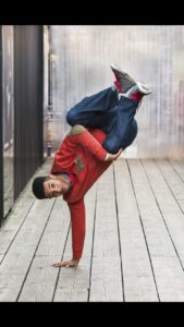 Nathan Geering, a mixed race man of afro carribean and British descent is wearing an orange sweat shirt with a patchwork pocket on his chest and elbow pads that are patchwork also. He has navy blue jeans and grey shoes with red shoelaces. He is balancing upside down on his right hand with both of his knees tucked into his chest as he executes a handstand freeze on one hand.