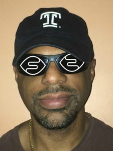 "!T.Reid wearing a hat with a ""T"" while the Seeing AI logo is imposed on his shades!"