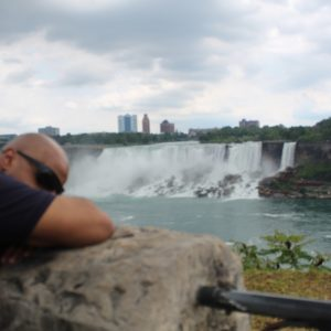 TReid sleeping on a large rock during a bright sunny day while in the background the Niagara Falls flows.