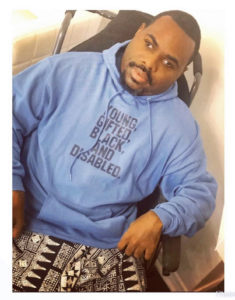 "AJani AJ Murray , a Black male with short haircut & facial hair seated in a wheelchair. He wears black & white print baggie pants with a blue long sleeve hoodie with words printed in black: ""Young, gifted, black and disabled."""
