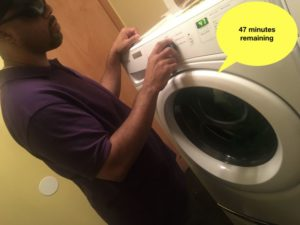 "TReid in front of washing machine which appears to be talking... machine says ""47 minutes remaining on the wash cycle!"